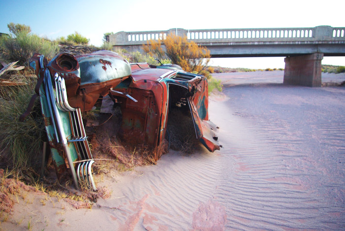 old car on banks of Dead River - bridge in background